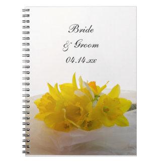Narcisos amarillos en el cuaderno espiral del boda