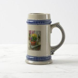 Narcisos y pensamientos en maceta taza de café