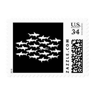 Natación del buceador con una escuela de tiburones sellos postales