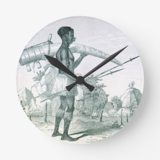 Native carrying a decorated ivory elephant tusk, f round clock