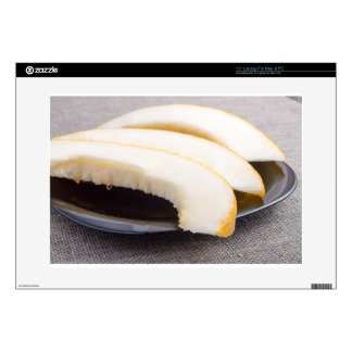Natural pieces of yellow melon on a black plate laptop skin