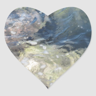 Nature background of transparent sea water flowing heart sticker