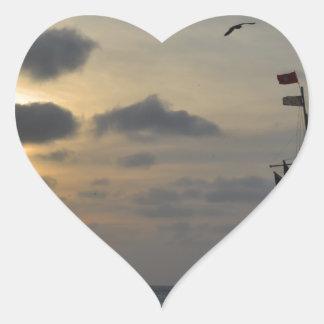 Navegación en la puesta del sol pegatina en forma de corazón