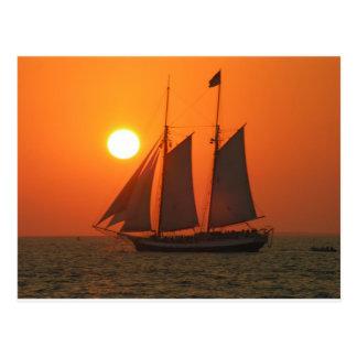 Navegue en la puesta del sol postales