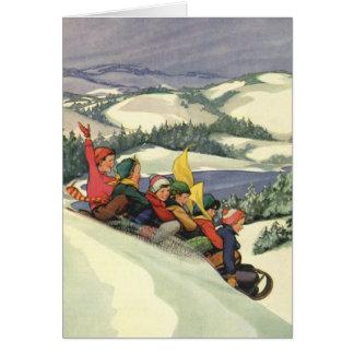 Navidad del vintage, niños Sledding en una montaña Tarjetón