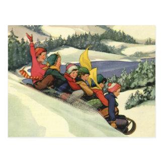 Navidad del vintage, niños Sledding en una montaña Tarjeta Postal