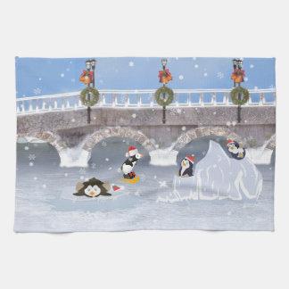 Navidad, pingüinos juguetones en el lago congelado toallas de cocina