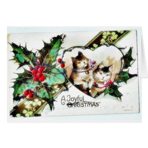 Navidad que saluda con dos gatos y cintas alrededo tarjetón