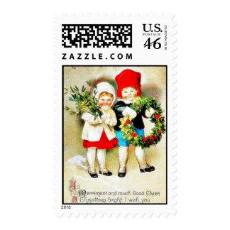 Navidad que saluda con dos niños que llevan a cabo sellos
