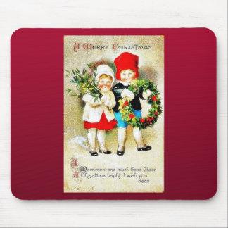 Navidad que saluda con dos niños que llevan a cabo alfombrillas de ratones