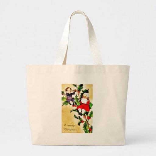 Navidad que saluda con dos niños que se sientan en bolsas