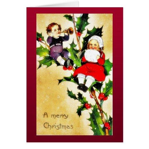 Navidad que saluda con dos niños que se sientan en tarjetón