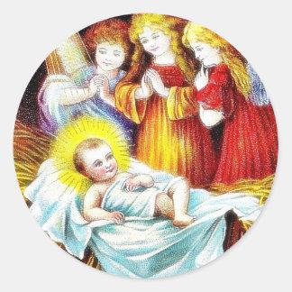Navidad que saluda con los ángeles que ruegan el pegatina redonda