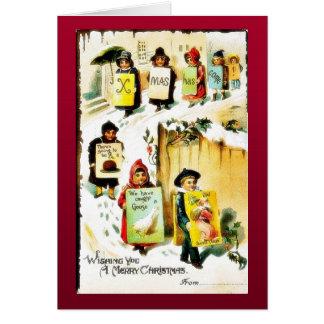 Navidad que saluda con los niños que llevan el jue tarjeta de felicitación