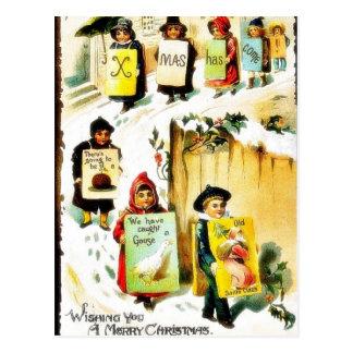 Navidad que saluda con los niños que llevan el jue postal