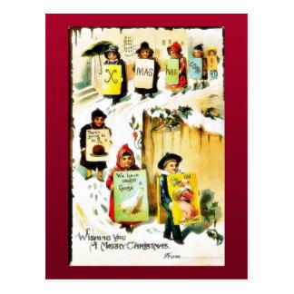 Navidad que saluda con los niños que llevan el jue postales