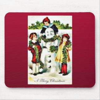 Navidad que saluda con tres niños que llevan un ga alfombrilla de ratón