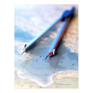 Navigation. Dividers sitting on a map. Postcard