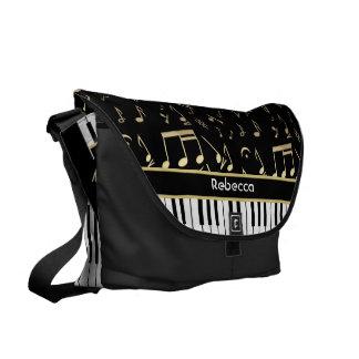 Negro y oro de las notas musicales y de las llaves bolsas de mensajeria