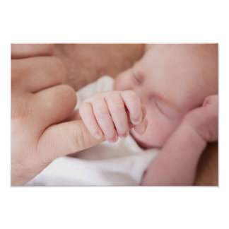 newborn baby holding fathers finger poster