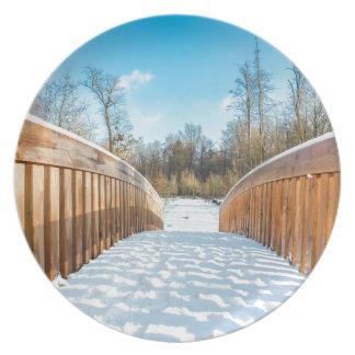 Nieve en el puente de madera en bosque platos de comidas