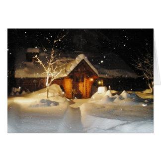 Nieve que cae en cabaña de madera en la tarjeta de