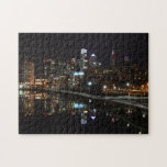 "Night in Philly Jigsaw Puzzle<br><div class=""desc"">This night photo of the city of Philadelphia was taken from a bridge crossing the Schuylkill River. The Schuylkill Banks riverwalk runs along the bank of the river closer to Center City,  while the blurred lines of cars traveling on the Schuylkill Expressway can be seen on the left.</div>"