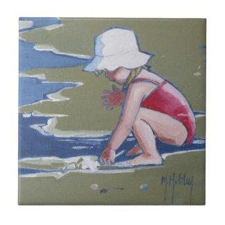 Niña con el gorra en la playa con las ondas azulejo cerámica