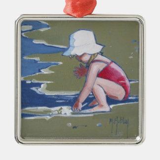 Niña con el gorra en la playa con las ondas adorno cuadrado plateado