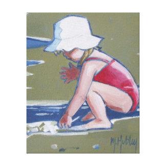 Niña con el gorra en la playa con las ondas impresiones en lienzo estiradas