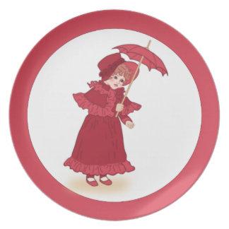 Niña con la placa del paraguas plato de comida