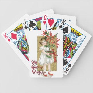 Niña con las flores del navidad barajas de cartas
