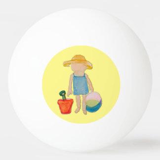 Niña del niño del amarillo de mantequilla en la pelota de ping pong