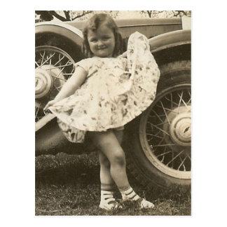 niña en coche con la postal del vestido
