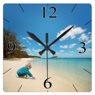 Niña en la playa con los Seashells Relojes De Pared