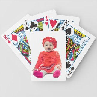 Niña en vestido rojo barajas de cartas