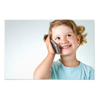 Niña feliz que habla por el teléfono celular impresión fotográfica