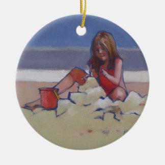 Niña linda del niño de la arena que juega en la adorno navideño redondo de cerámica