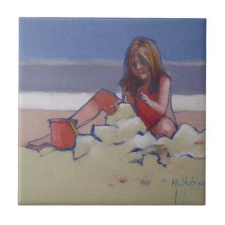 Niña linda del niño de la arena que juega en la pl teja  ceramica