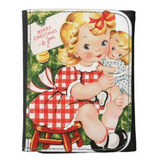 Niña linda del vintage con una muñeca
