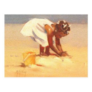 Niña linda que juega en arena postales