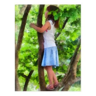 Niña que juega en árbol postal