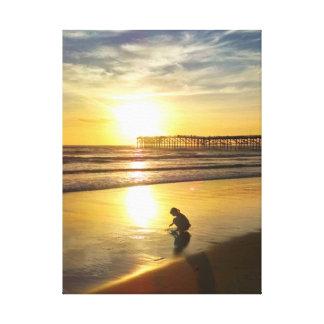 Niña que juega en la playa en la puesta del sol impresión en lienzo estirada