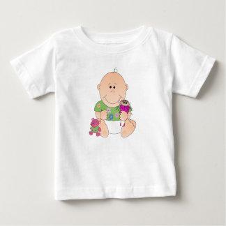 Niña sonriente linda con la muñeca del het y la t-shirts