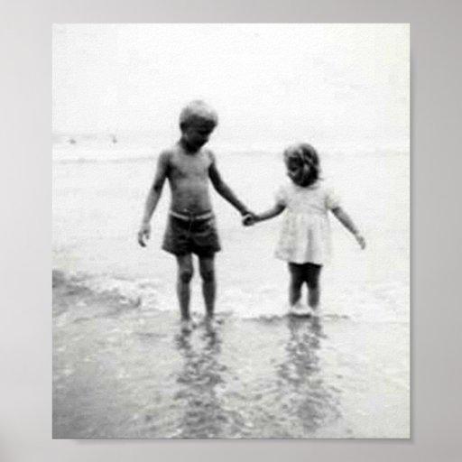 Niña y muchacho que sostienen el pequeño poster de