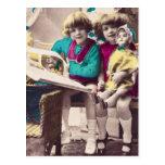 Niñas coloreadas mano que leen el vintage postales
