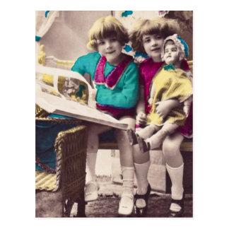 Niñas coloreadas mano que leen el vintage postal