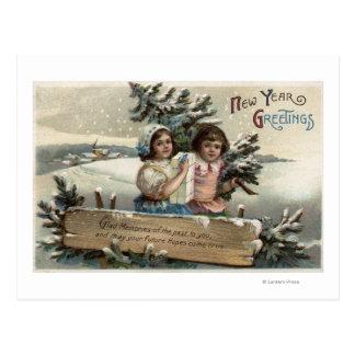 Niñas que sostienen un presente y un árbol postales