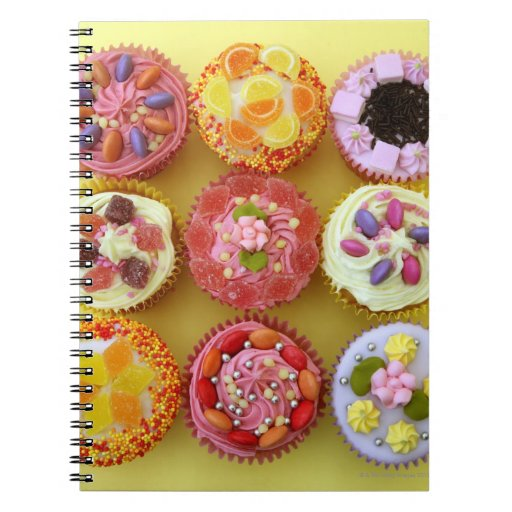 Nine cupcakes each decorated with candy in a notebook