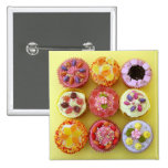 Nine cupcakes each decorated with candy in a pinback button